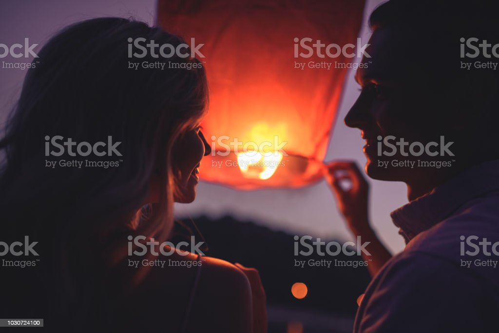 portrait of couple launching sky lantern on river beach in evening and looking at each other stock photo