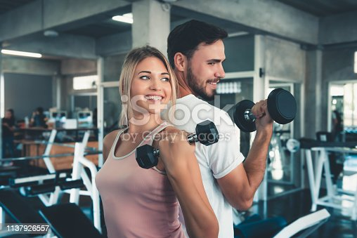 Portrait of Couple Love in Fitness Training With Dumbbell Equipment., Young Couple Caucasian are Working Out and Training Together in Gym Club., Sport and Healthy Concept.
