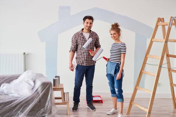 Retrato de pareja pintando la pared interior en apartamento nuevo - foto de stock