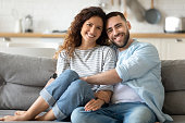istock Portrait of couple posing photo shooting seated on couch indoors 1198401599