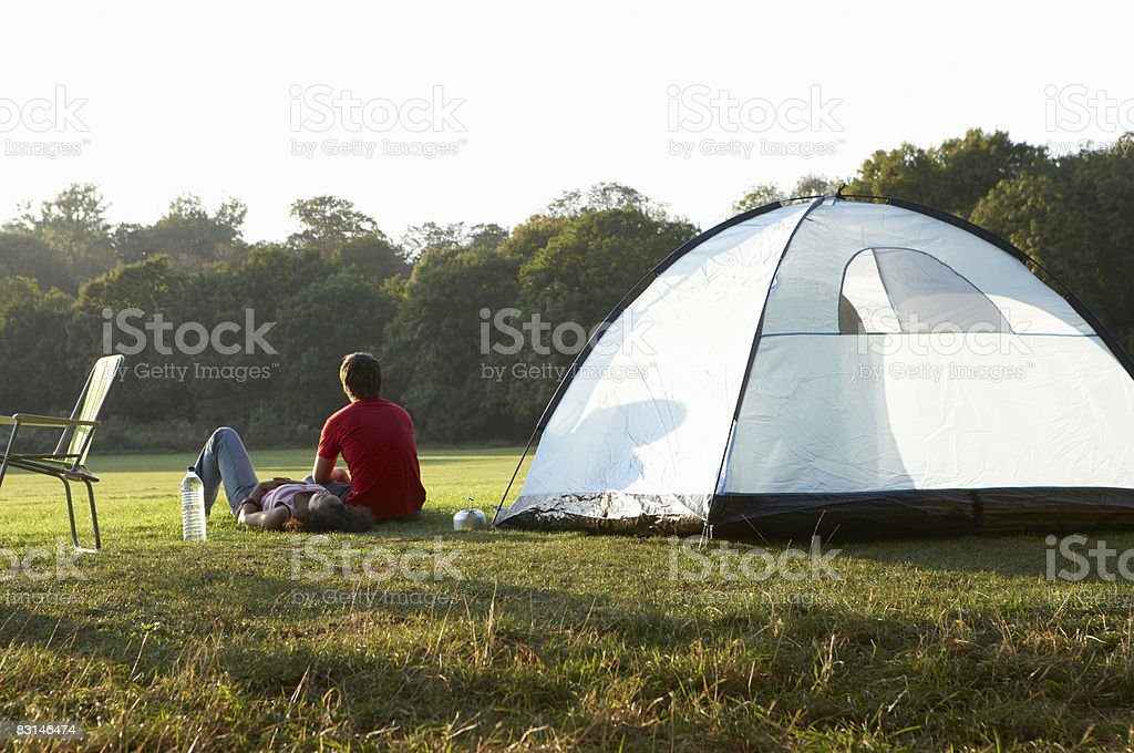 Portrait of couple sitting by tent royalty free stockfoto