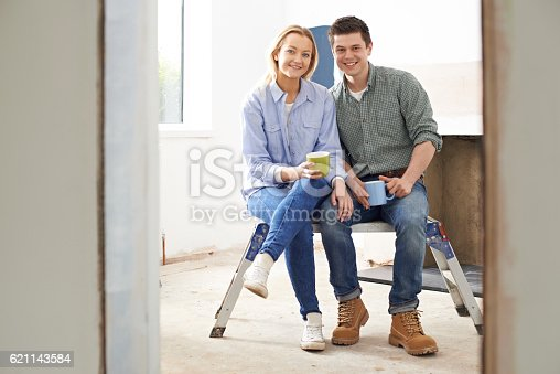 Portrait Of Couple Sitting In Property Being Rennovated