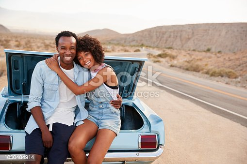 1030408008istockphoto Portrait Of Couple Sitting In Trunk Of Classic Car On Road Trip 1030404914