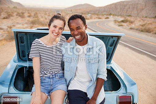 1030408008istockphoto Portrait Of Couple Sitting In Trunk Of Classic Car On Road Trip 1030405004