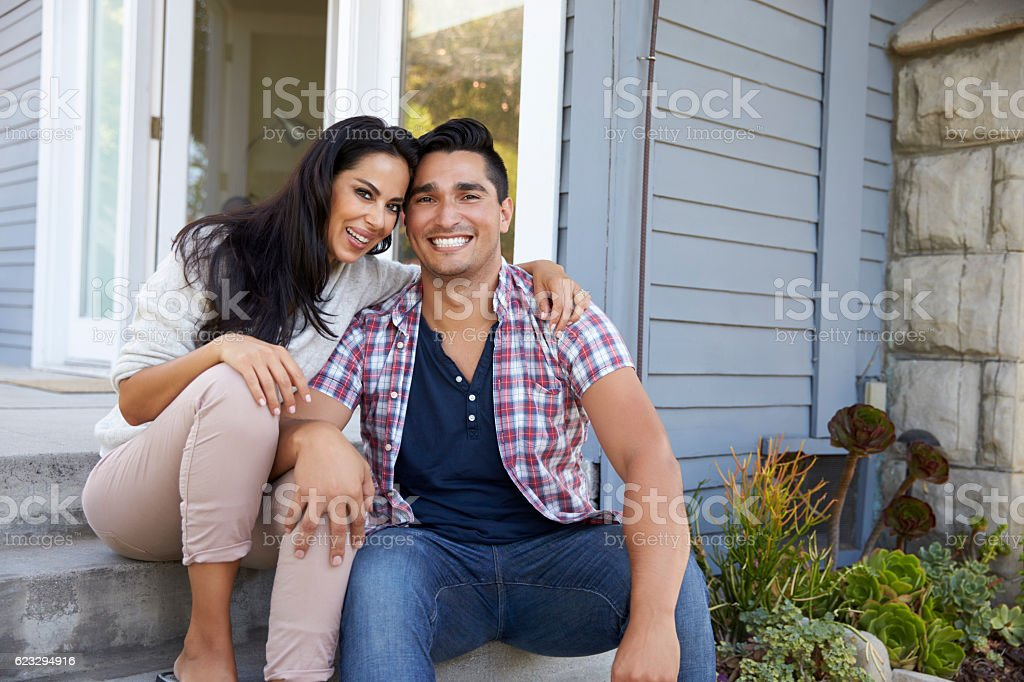 Portrait Of Couple Sitting On Steps Outside Home stock photo