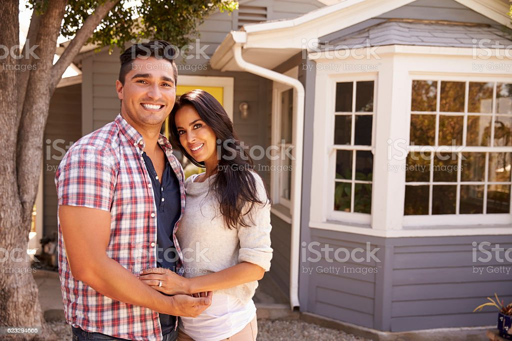 Portrait Of Couple Standing Outside Home stock photo