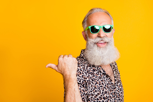 istock Portrait of crazy bearded old man point at copyspace recommend promo ads feel funny, funky wearing leopard shirt green eyeglasses eyewear isolated over yellow 1174134181