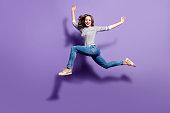 紫色の背景、人々 生活エネルギー ライフ スタイル コンセプトに分離されて良いストレッチを持つカメラを見て空気を跳び越える狂気の愚かな少女の肖像画