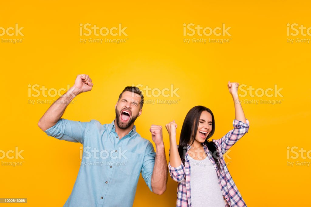 Portrait of crazy man couple full of happiness yelling loudly holding raised arms keeping eyes closed celebrating victory isolated on vivid yellow background royalty-free stock photo