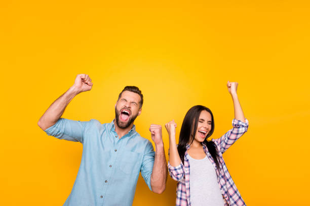 portrait of crazy man couple full of happiness yelling loudly holding raised arms keeping eyes closed celebrating victory isolated on vivid yellow background - celebration stock pictures, royalty-free photos & images
