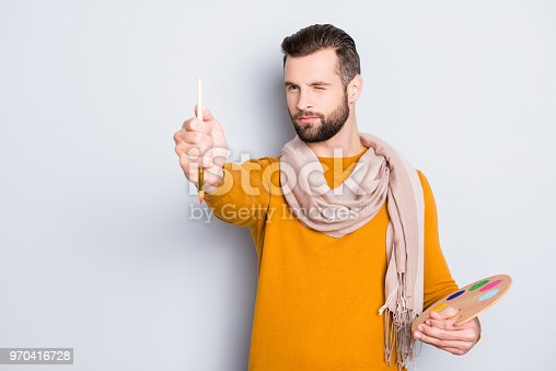 636761588istockphoto Portrait of creative concentrated artist with bristle in sweater and scarf on neck using, having colorful palette, brushed in arms, analyzing, expertising pic, isolated on grey background 970416728