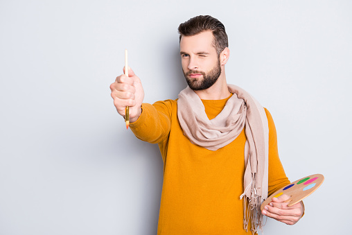 636761588 istock photo Portrait of creative concentrated artist with bristle in sweater and scarf on neck using, having colorful palette, brushed in arms, analyzing, expertising pic, isolated on grey background 970416728