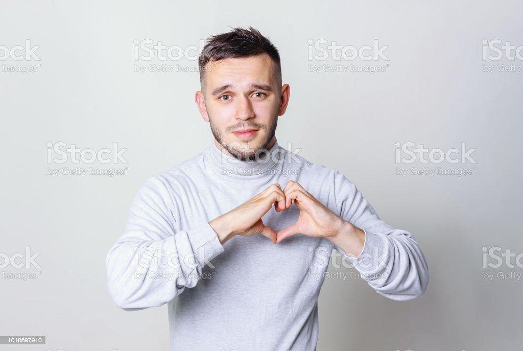 Retrato de hombre soñador creativo con figura de corazón que hace de pelo negro amor signo con los dedos que tentadora seductora vista mirando a cámara aislada sobre fondo gris - foto de stock