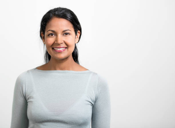 Portrait of creative Indian businesswoman smiling Portrait of Indian businesswoman smiling. Close-up of beautiful female professional is against white background. She is wearing smart casuals. one mid adult woman only stock pictures, royalty-free photos & images