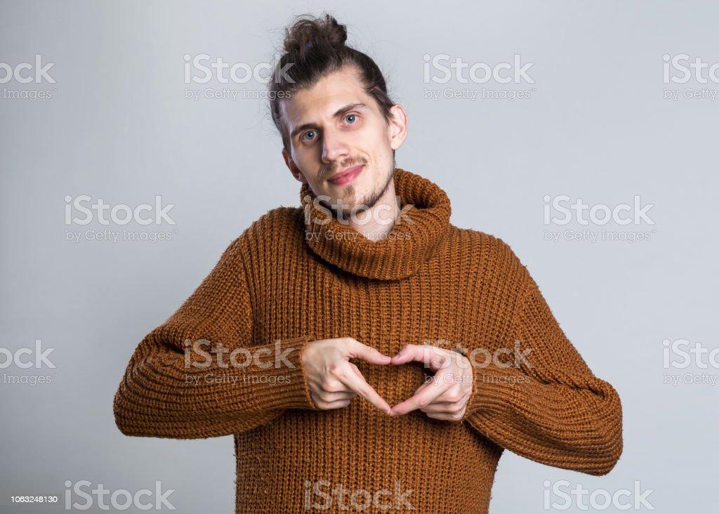 Retrato de hombre creativo en una figura de corazón hacer Jersey de punto cálido amor signo con los dedos que tentadora seductora vista mirando a cámara en fondo gris - foto de stock