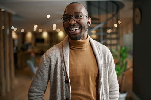 Happy portrait of african entrepreneur laughing and smiling. feeling excited and positive. Wearing trendy clothing and eye glasses in a modern working space