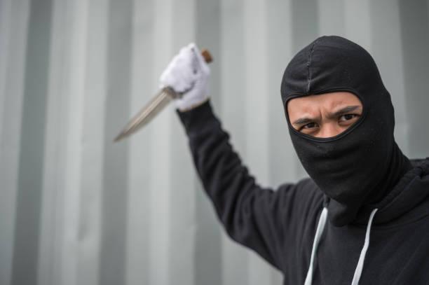 porträt von straf- oder bandit tragen schwarze maske hält ein messer und blick auf kamera, konzept der halsabschneider und mörder - hackmesser stock-fotos und bilder