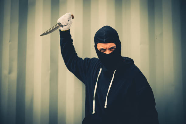 portrait of criminal or bandit wear black mask holding a knife and looking to camera, concept of cutthroat and assassin portrait of criminal or bandit wear black mask holding a knife and looking to camera, concept of cutthroat and assassin cutthroat stock pictures, royalty-free photos & images