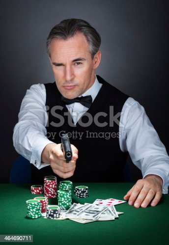 istock Portrait of croupier aiming with a gun 464690711