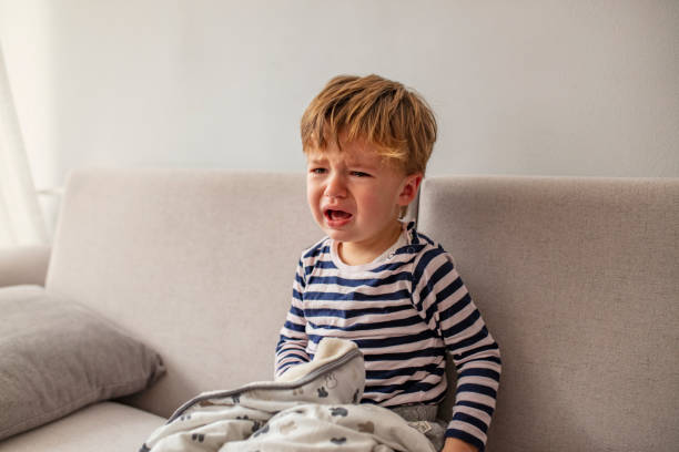 Portrait of crying baby boy No! Little African baby boy crying while seating on the couch at home. Portrait of crying baby boy. Baby's crying one year old, brunette with brown eyes, hysteria, the crisis of the first year of life. crying stock pictures, royalty-free photos & images