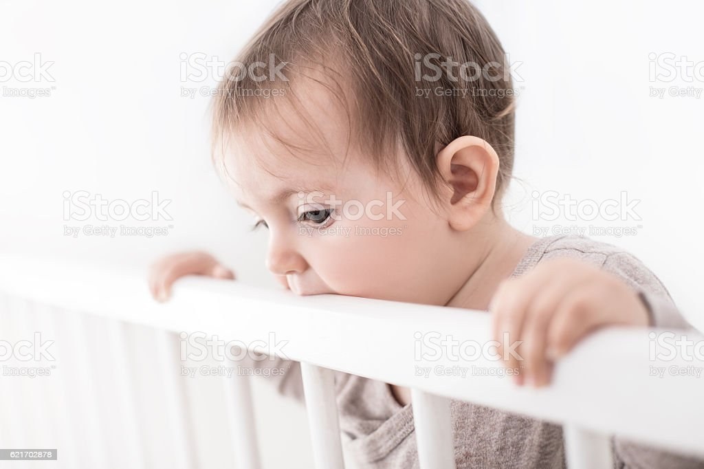 Portrait of cure baby in his cot, isolated on white stock photo