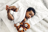 istock Portrait of cute adorable little african american baby sleep in a white bedroom 1216315229