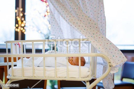 istock Portrait of cute adorable newborn baby girl in birth hospital. 1034954948