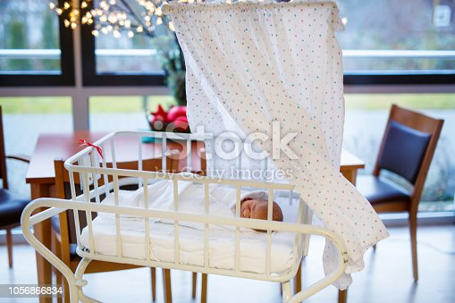 istock Portrait of cute adorable newborn baby girl in birth hospital. 1056866834