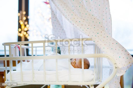 istock Portrait of cute adorable newborn baby girl in birth hospital. 695467266