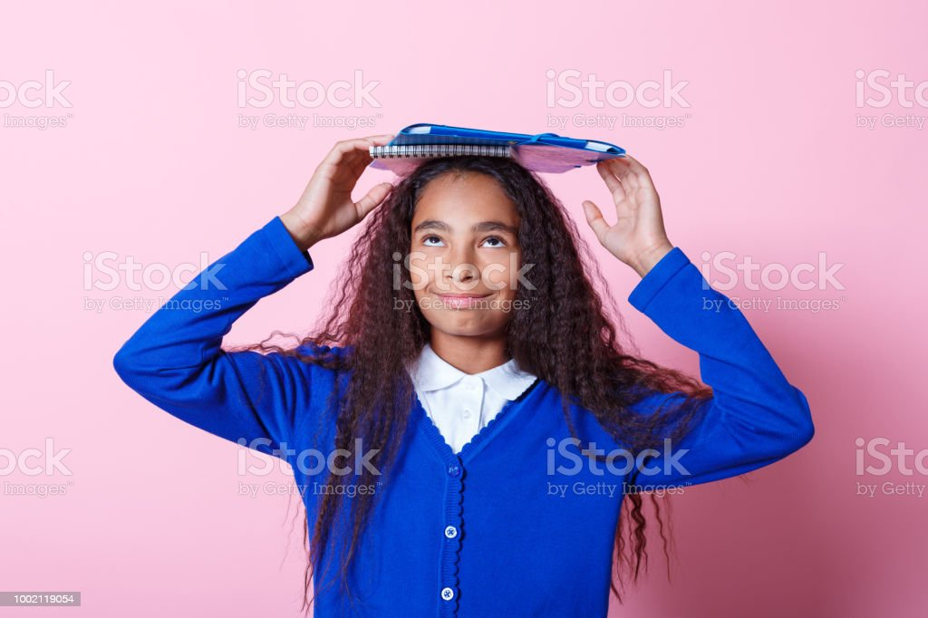 Portrait of cute afro amercian schoolgirl Afro American schoolgirl wearing school uniforms holding workbooks on her head, looking up. Studio shot, pink background. 10-11 Years Stock Photo