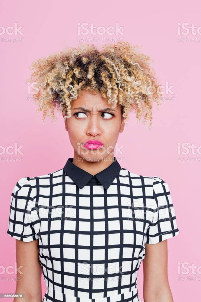 Portrait of cute afro american young woman wondering Studio portrait of cute afro american young woman wondering. Pink background. 20-24 Years Stock Photo