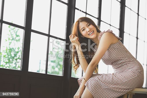istock Portrait of cute and beautiful Asian girl smiling in coffee shop or modern office with copy space. Happy people, modern lifestyle, or women fashion advertisement concept 943759290