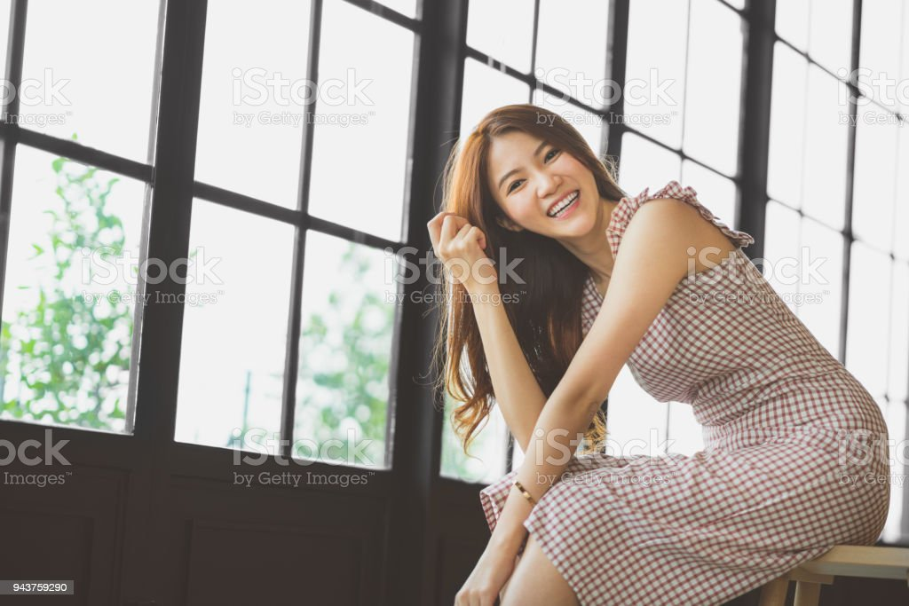 Portrait of cute and beautiful Asian girl smiling in coffee shop or modern office with copy space. Happy people, modern lifestyle, or women fashion advertisement concept stock photo