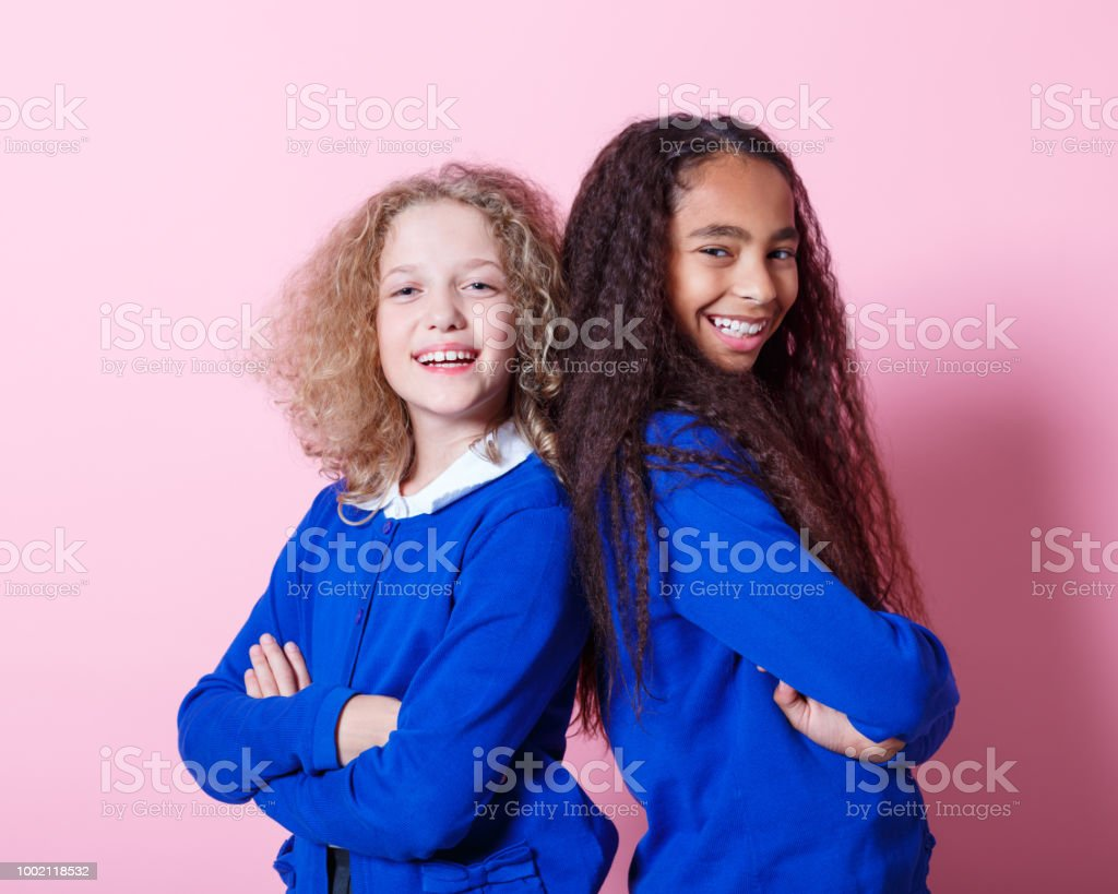 Portrait of cute and happy multi ethnic schoolgirls Two multi ethnic schoolgirls wearing school uniforms standing back to back with arms crossed and smiling at camera. Studio shot, pink background. 10-11 Years Stock Photo