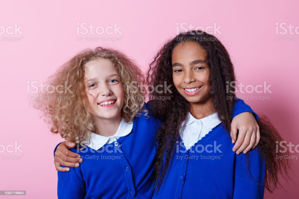 Portrait of cute and happy multi ethnic schoolgirls Two multi ethnic schoolgirls wearing school uniforms embracing and smiling at camera. Studio shot, pink background. 10-11 Years Stock Photo