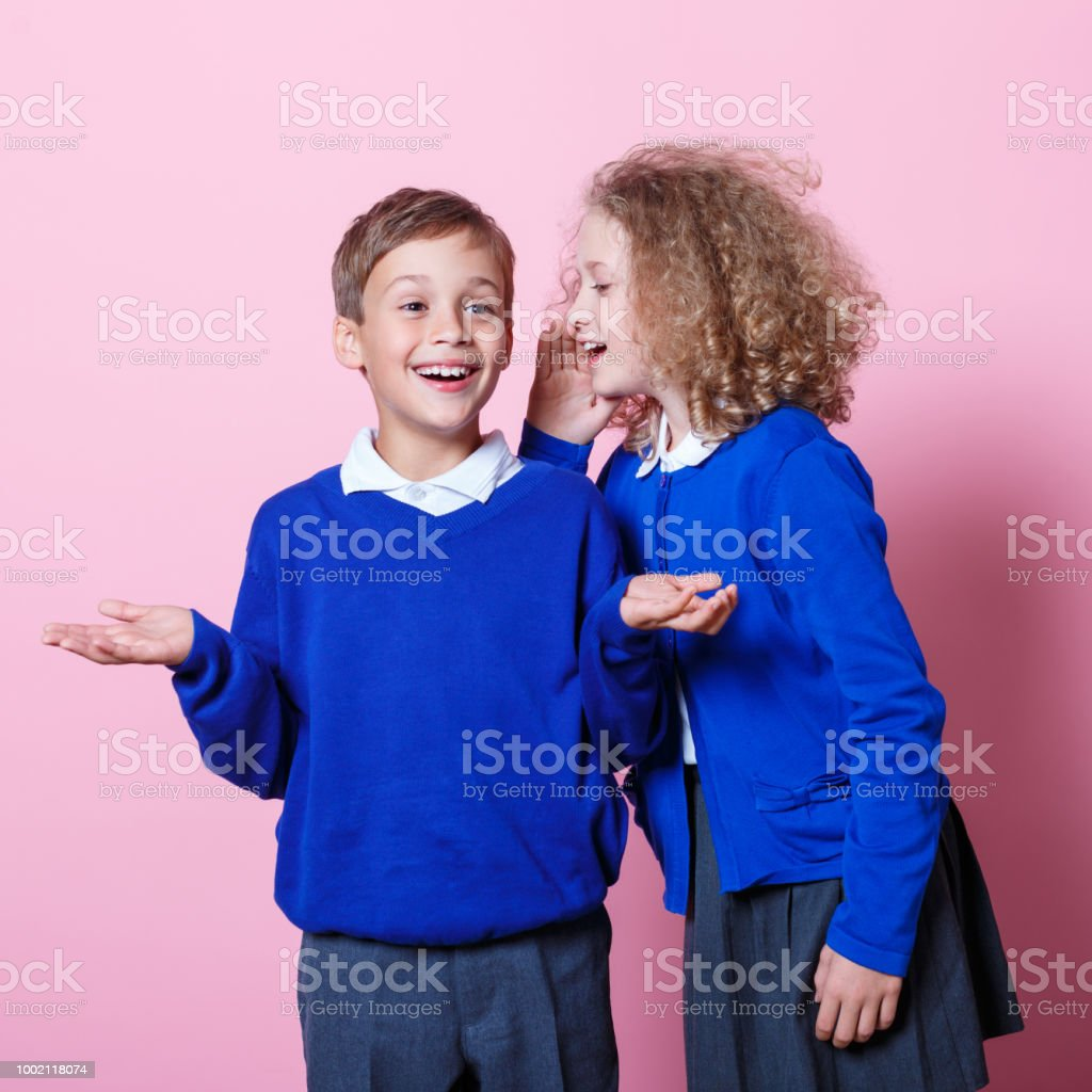 Portrait of cute and happy schoolboy and schoolgirl Schoolgirl whispering to her cute school friend. Studio shot, pink background. 8-9 Years Stock Photo