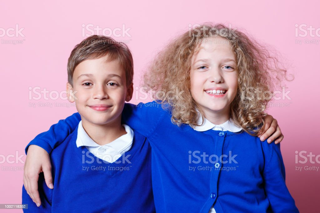 Portrait of cute and happy schoolboy and schoolgirl Happy school children wearing school uniforms embracing and smiling at the camera. Studio shot, pink background. 8-9 Years Stock Photo