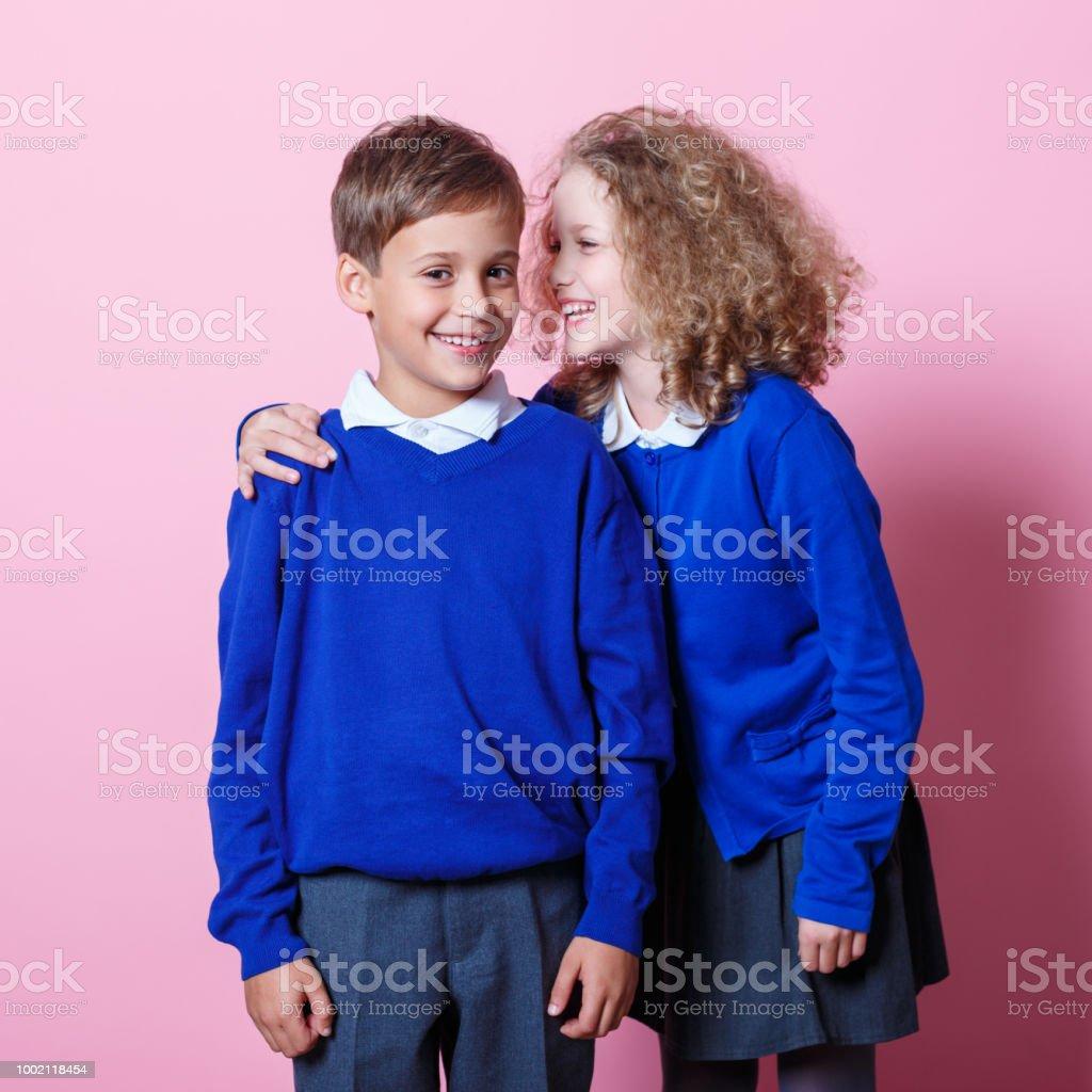 Portrait of cute and happy schoolboy and schoolgirl Schoolgirl whispering to her cute school friend. Studio shot, pink background. 8-9 Years Stock Photo