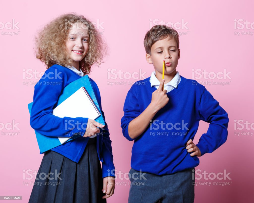 Portrait of cute and happy schoolboy and schoolgirl Happy school children wearing school uniforms standing against pink background. Girl holding exercise book. Studio shot. 8-9 Years Stock Photo