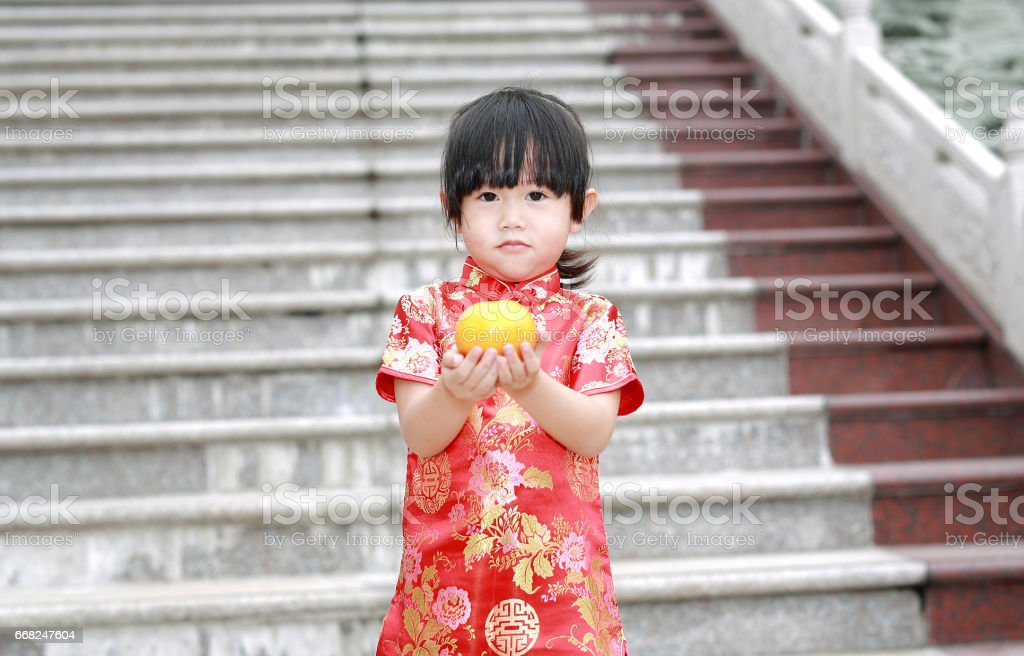 Portrait of Cute asian kid girl in Red Traditional Chinese dress with holding sacred Orange at chinese temple in bangkok thailand. foto stock royalty-free