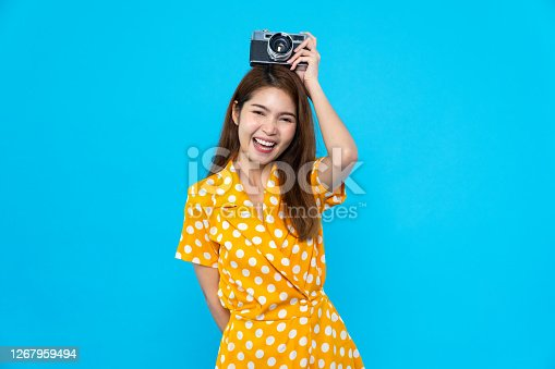 Portrait of cute Asian woman smiling, holding retro camera with funny pose. Happy people, colorful summer fashion, or travel lifestyle concept
