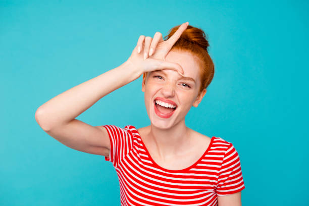 Portrait of cute attractive cheerful stylish trendy glad red-haired girl with bun, wearing t-shirt, opened mouth, showing loser sign, isolated on teal pastel bright vivid blue background Portrait of cute attractive cheerful stylish trendy glad red-haired girl with bun, wearing t-shirt, opened mouth, showing loser sign, isolated on teal pastel bright vivid blue background nerd hairstyles for girls stock pictures, royalty-free photos & images