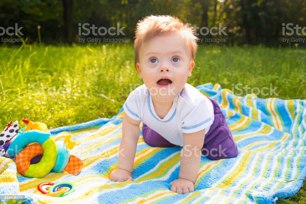 Portrait of Cute baby boy with Down syndrome lying on blanket in summer day on nature stock photo