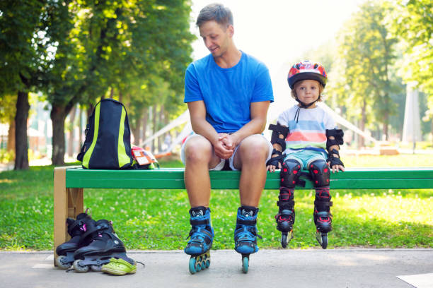 Portrait of cute baby boy with inline skating instructor. stock photo