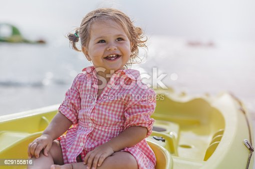 istock Portrait of cute baby girl on vacation sitting in canoe 629155816