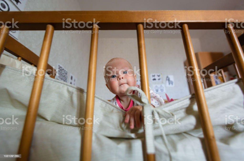 Porträt von niedlichen Babymädchen mit blauen Augen sitzt in der Krippe. Adorable Baby sitzt allein im Kinderbett und ist interessiert Umgebung. Konzept der Wahrnehmung der Welt von Kindern. – Foto
