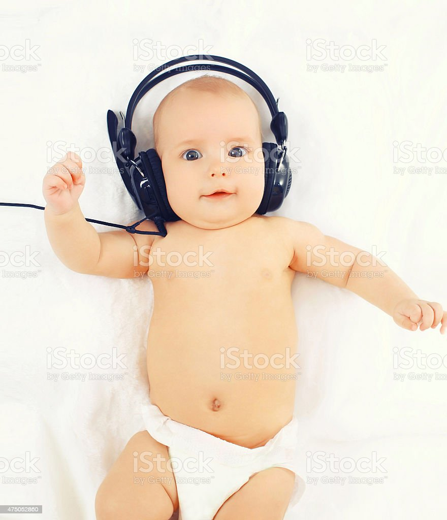 Portrait of cute baby listens to music in headphones lying stock photo