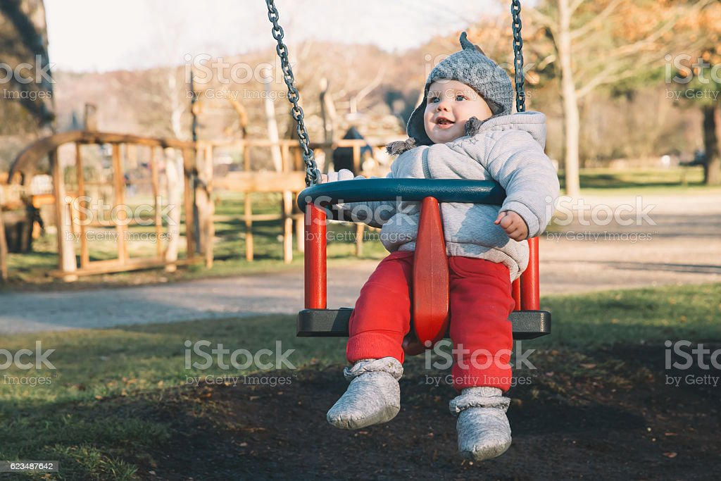Portrait of cute baby on swing, outdoors. stock photo