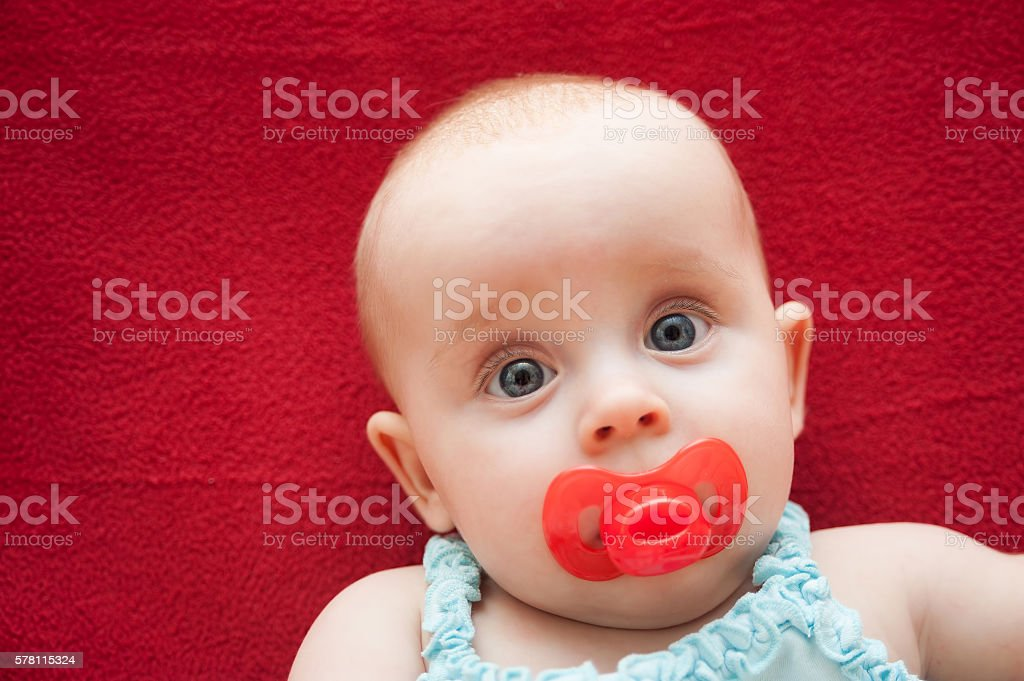 portrait of cute baby with pacifier in her mouth stock photo more