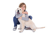 Portrait of cute boy hugging his dog on white background